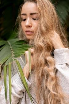 Hermosa mujer posando junto a las hojas