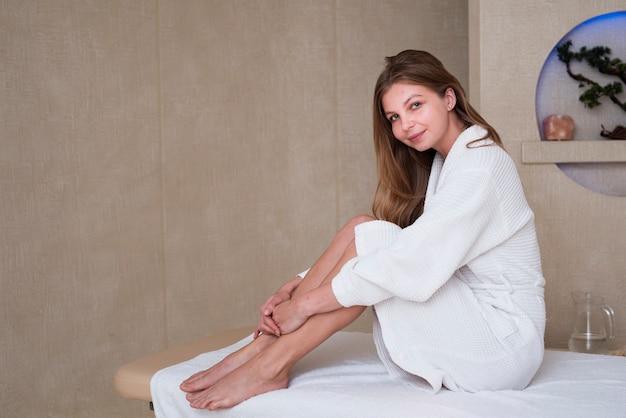 Hermosa mujer posando en la mesa de masaje en el spa