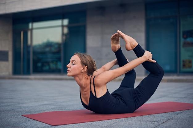 Hermosa mujer practica yoga asana dhanurasana - pose de arco al aire libre  | Foto Premium