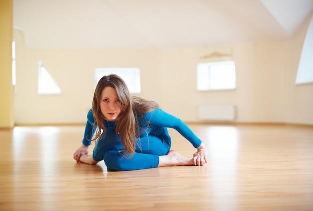 Hermosa mujer practica yoga asanas agnistambhasana. pose de registro de fuego en el estudio de yoga