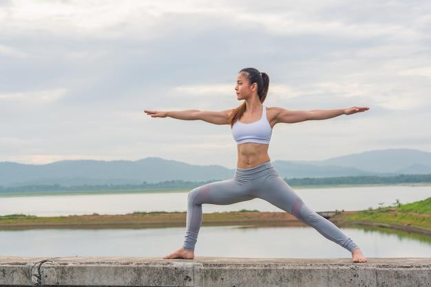 Hermosa mujer practicando yoga junto al lago con la montaña.