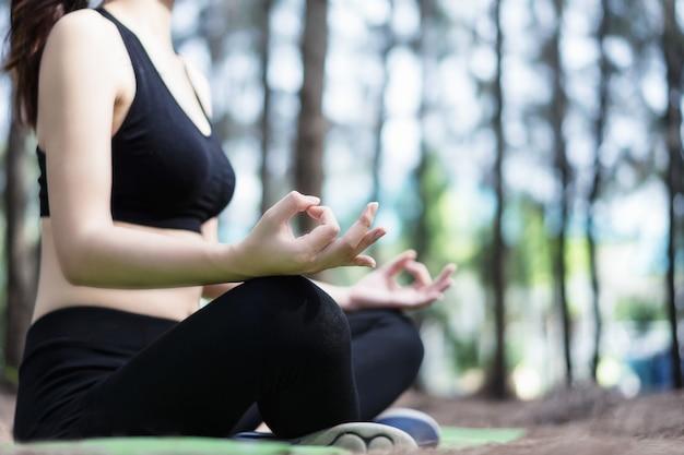 Hermosa mujer está practicando yoga en el parque