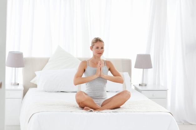 Hermosa mujer practicando yoga en su cama