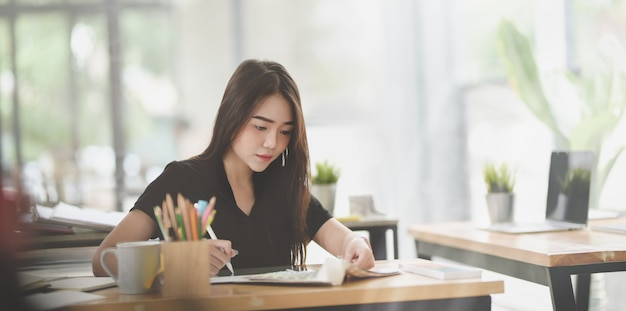 Hermosa mujer profesional independiente escribiendo su idea en el cuaderno