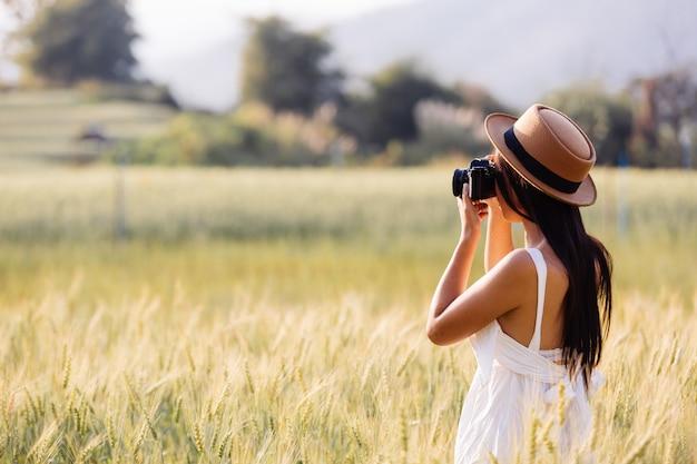 Una hermosa mujer que disfruta disparando en campos de cebada.