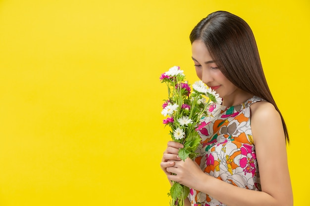 Hermosa mujer que huele a flor blanca