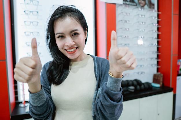 Una hermosa mujer que sonríe está en una clínica oftalmológica dando recomendaciones a la clínica, así como una vitrina de anteojos de fondo.