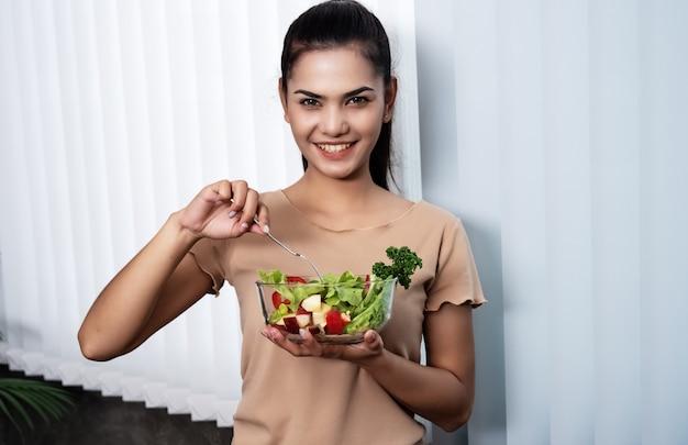 La hermosa mujer que sostiene el tazón de ensalada en la mano, al lado de la ventana, con una sonrisa y un sentimiento feliz, se prepara para comer, buena para la dieta y la salud