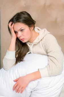 Hermosa mujer que tiene un dolor de cabeza en la cama
