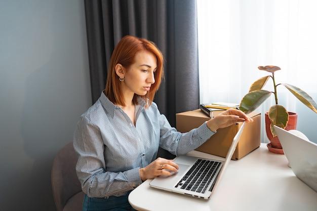 Hermosa mujer que trabaja en la computadora portátil, área de trabajo compartido