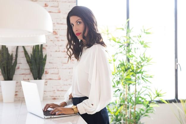 Hermosa mujer que trabaja en la computadora portátil