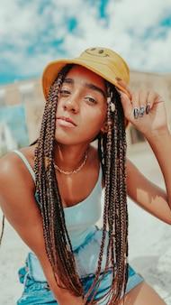 Hermosa mujer con rastas en un sombrero de cubo posando en la cámara