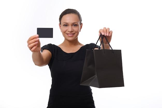 Hermosa mujer de raza mixta mira a la cámara y sonríe con una sonrisa con dientes, mostrando un paquete de compras negro y una tarjeta de crédito o descuento de plástico en sus manos extendidas. concepto de black friday con espacio de copia