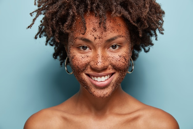 Hermosa mujer de raza mixta tiene exfoliación en la piel en la cara, sonríe suavemente, hace máscaras cosméticas de café, tiene peinado rizado, hombros desnudos, aislado sobre una pared azul