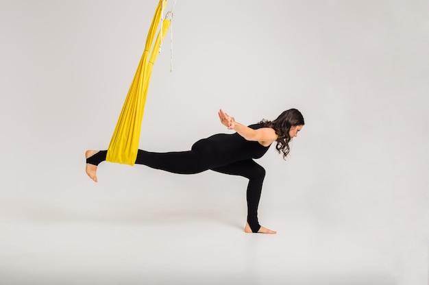 Una hermosa mujer realiza una pose de yoga antigravedad en una hamaca amarilla sobre una pared blanca aislada con una copia del espacio