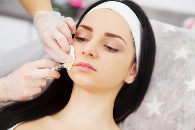 Hermosa mujer recibe inyecciones, cosmetología