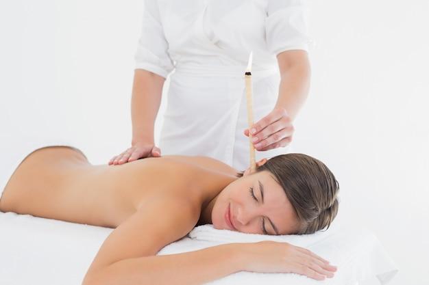 Hermosa mujer recibe tratamiento de vela oreja en el centro de spa