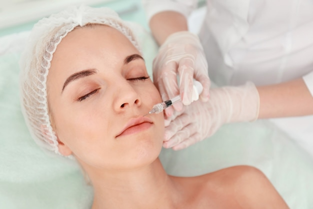 Hermosa mujer recibiendo una inyección en la cara