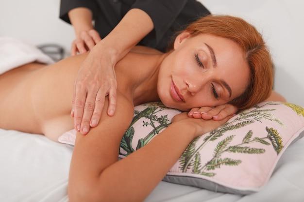 Hermosa mujer recibiendo masaje relajante en el spa center