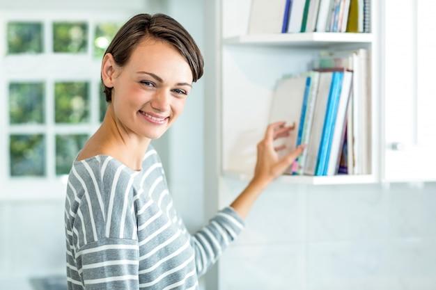 Hermosa mujer recogiendo libro del gabinete en casa