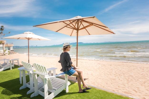 Hermosa mujer se relaja en la playa, bajo paraguas