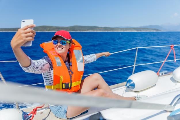 Hermosa mujer relajándose y haciendo un selfie en yate en grecia