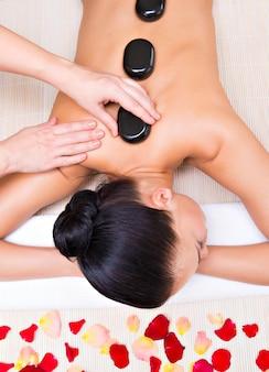 Hermosa mujer relajante en el salón de spa con piedras calientes en el cuerpo. terapia de tratamientos de belleza