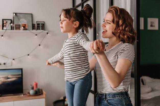 Hermosa mujer rizada en camiseta a rayas levantó a su hija alto y jugando con ella.
