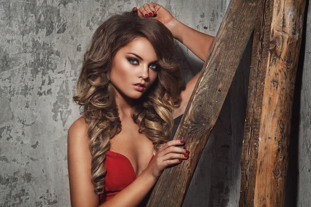 Hermosa mujer rizada en vestido rojo
