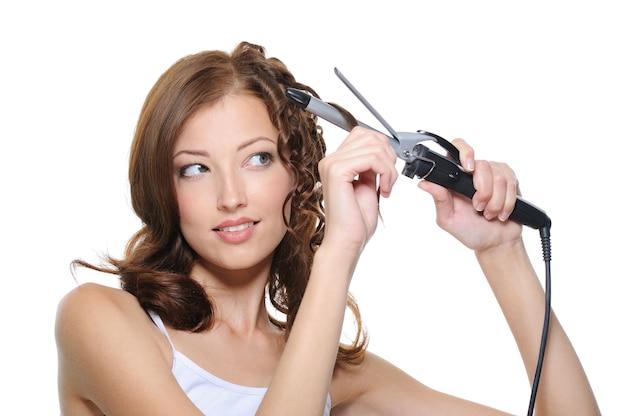 Hermosa mujer rizando su cabello morena con rodillo aislado en blanco