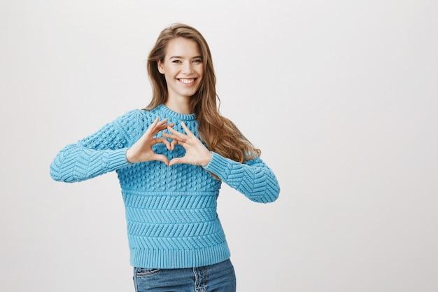 Hermosa mujer romántica sonriente muestra signo de corazón