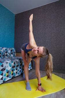 Hermosa mujer en ropa deportiva, pantalones cortos y un sostén de pie en una pose, ejercicios, chica atractiva practicando yoga, ejercitándose en casa o en un moderno estudio de yoga, estiramiento corporal