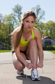 Hermosa mujer en ropa de fitness ata cordones de los zapatos
