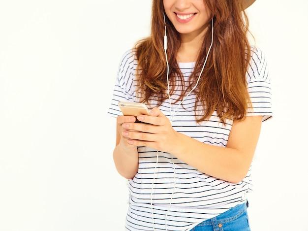 Hermosa mujer en ropa de verano casual hipster sin maquillaje en sombrero marrón escuchando música en el teléfono con auriculares aislados en blanco