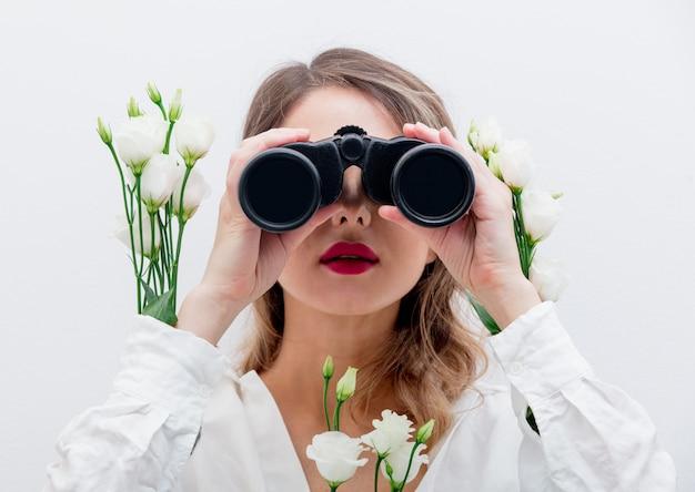 Hermosa mujer con rosas blancas en mangas con binoculares.
