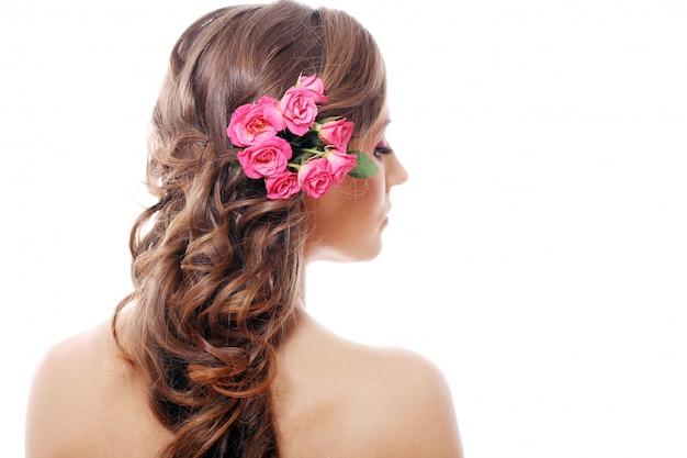 Hermosa mujer con rosas en el cabello