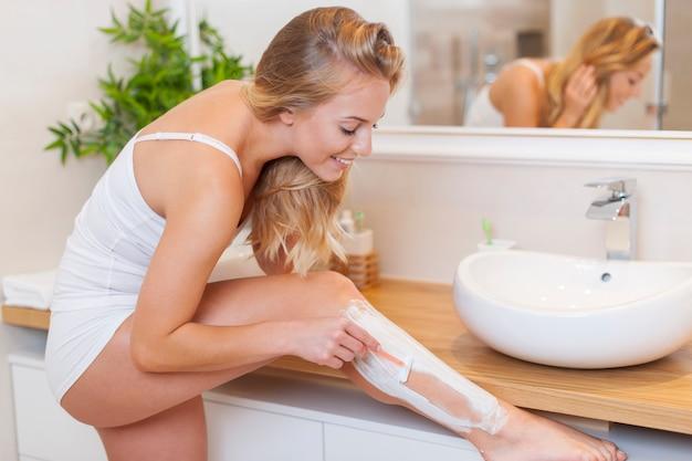 Hermosa mujer rubia afeitarse las piernas en el baño.