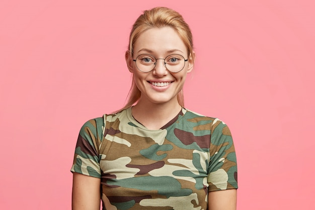 Hermosa mujer rubia alegre usa camiseta de camuflaje, gafas redondas, está en alto espíritu, sonríe con alegría, aislada sobre expresión rosa.