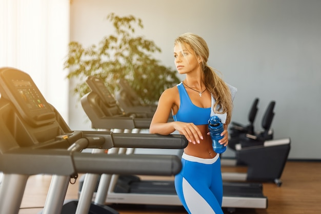 Hermosa mujer rubia atlética es beber agua en una cinta en el gimnasio
