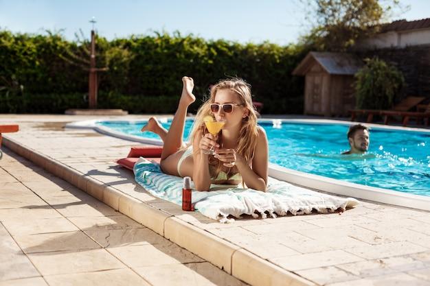 Hermosa mujer rubia bebiendo cócteles, tomando el sol, tumbado junto a la piscina