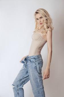 Hermosa mujer rubia con cabello largo en jeans.