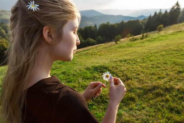 Hermosa mujer rubia con camomiles, fondo de montañas de los cárpatos