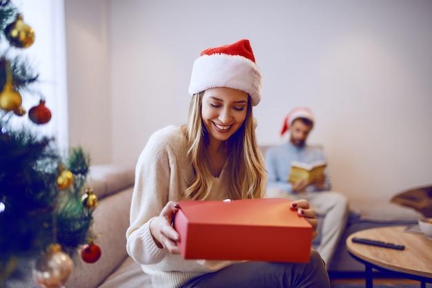 Hermosa mujer rubia caucásica sonriente en suéter blanco y con sombrero de santa en la cabeza sentado en la sala de estar y abriendo regalo de navidad en el fondo hombre leyendo el libro.