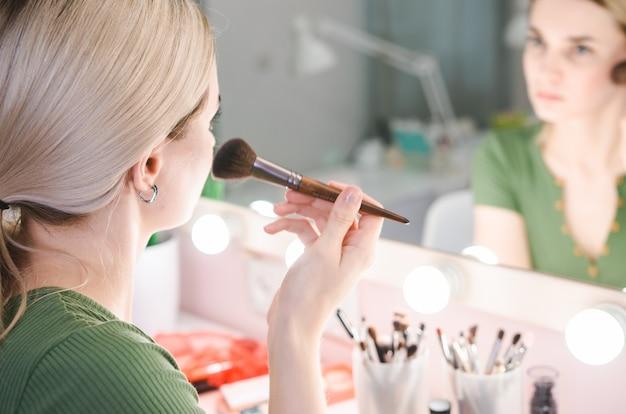 Hermosa mujer rubia cerca de espejo en la sala de maquillaje