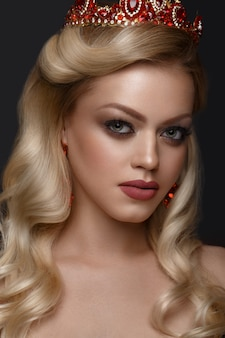 Hermosa mujer rubia con una corona de oro, aretes y maquillaje de noche profesional