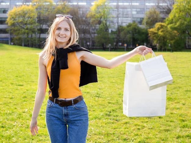 Hermosa mujer rubia disfruta de las compras. consumismo, maqueta de compras, concepto de estilo de vida