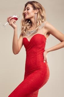 Hermosa mujer rubia elegante con vestido rojo de moda