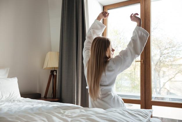 Hermosa mujer rubia estirando las manos en la mañana