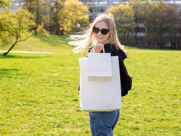Hermosa mujer rubia con gafas de sol disfruta de las compras. consumismo, maqueta de compras