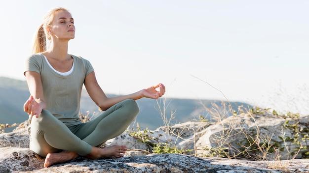 Hermosa mujer rubia haciendo yoga al aire libre
